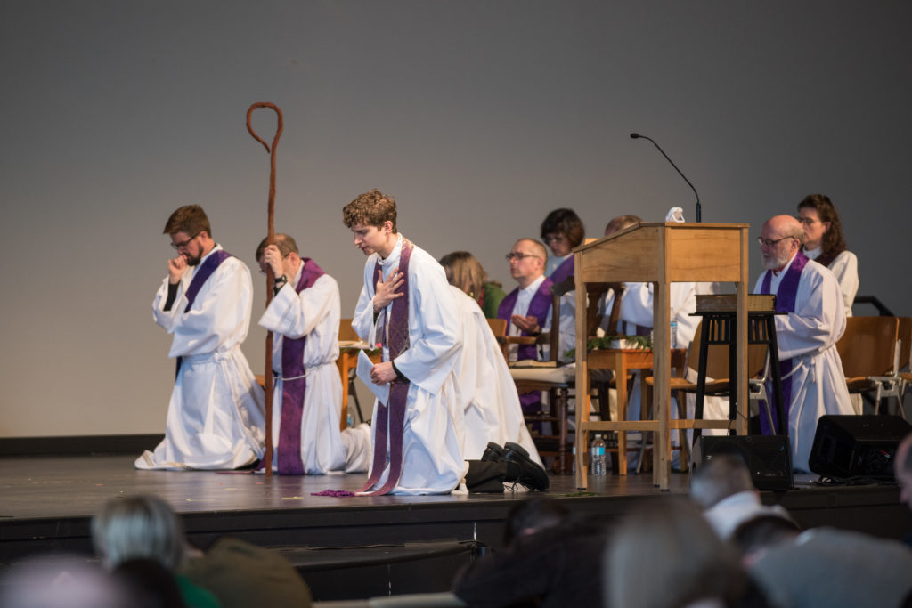 Kneeling clergy in robes on church stage