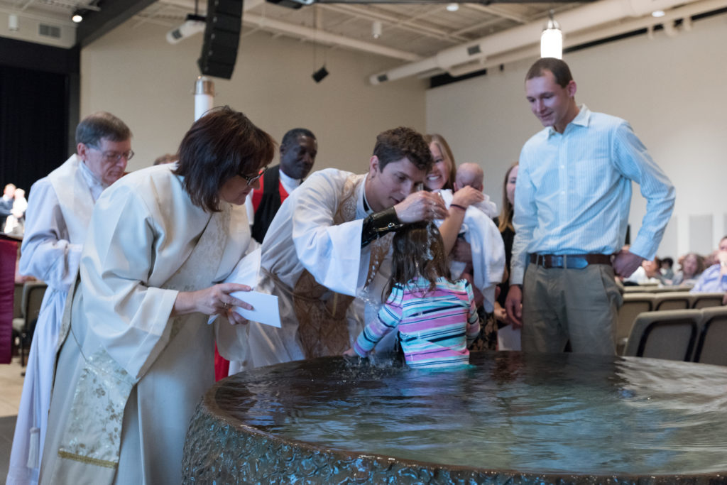 Anglican baptism service, child being baptized by priest